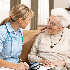 Nursing Healthcare - Nurse Speaks with Smiling Elderly Woman