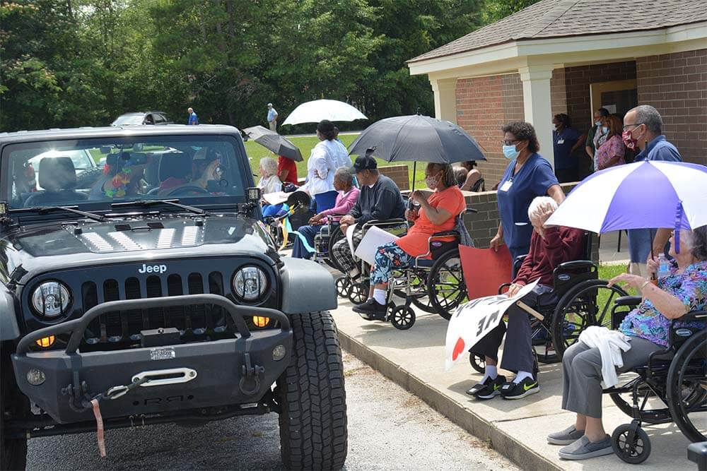 Pictures of family and friends in a drive through parade at the Williston Nursing Home in June of 2020